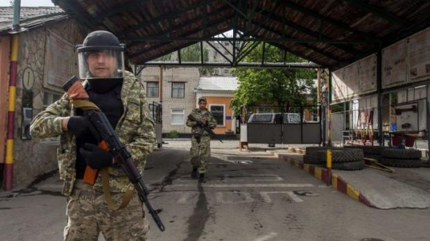 Win for separatists ... Pro-Russian militia men walk in an entrance to a border guards base, which they seized, on the ...