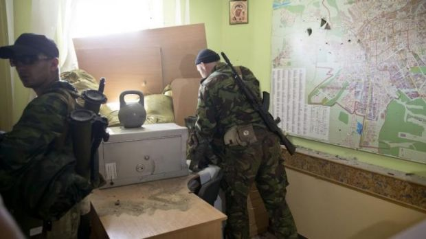 Pro-Russian rebels inspect the offices of an Ukrainian border troops military unit in Luhansk, eastern Ukraine, after ...