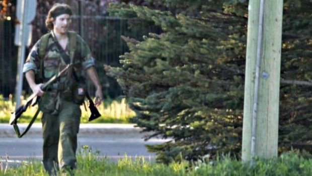 A heavily armed man that police have identified as Justin Bourque walks on Hildegard Drive in Moncton, New Brunswick, ...