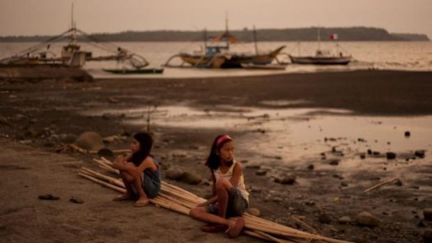 Hard times: Children sit in front of idle fishing boats on the shore of Masinloc, a town in the Philippines that depends ...