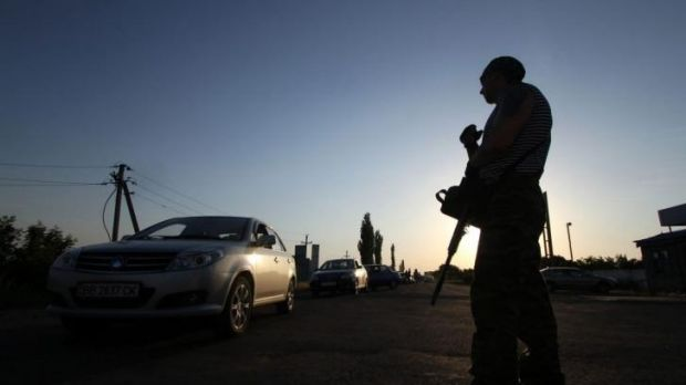 Tense: A pro-Russian militant stands guard at the Ukrainian-Russian border check-point near the city of Krasnopartizansk.