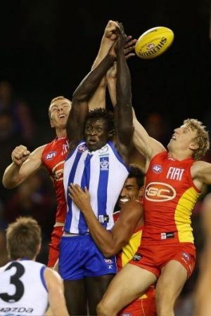 Rory Thompson (loeft) and Trent McKenzie of the Suns contest a mark with Majak Daw of North Melbourne in round seven.