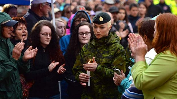Candlelight vigil: A Canadian soldier mourns the three dead Mounties in Moncton.