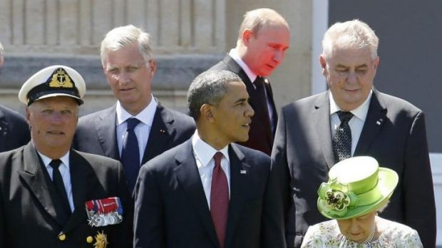 Russian President Vladimir Putin passes behind US President Barack Obama, Britain's Queen Elizabeth and Norway's King ...