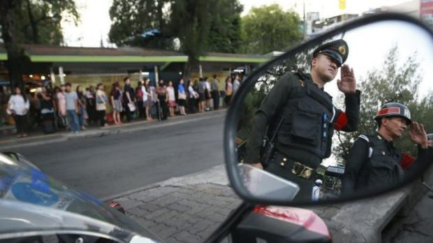 Thai military police listen to the national anthem at Bangkok's Victory Monument, which has been cleared of protesters ...