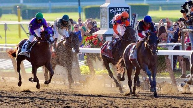 Victor Espinoza aboard California Chrome (2) ,left, rides past the finish line during the Belmont Stakes.
