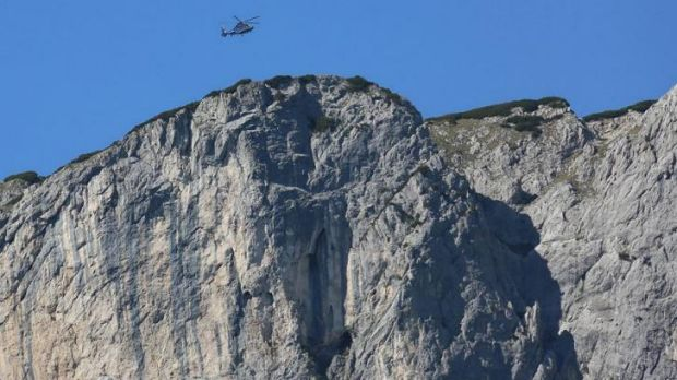 A helicopter flies above the Berchtesgaden Alps, where rescuers were working Monday to recover a man stuck deep inside a ...