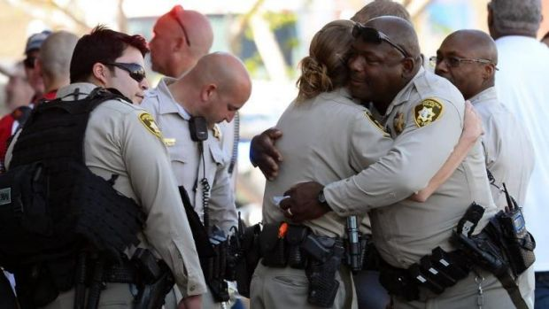 Las Vegas police officers hug near a Wal-Mart in the aftermath of the killings.