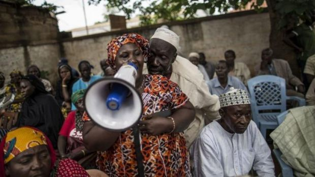Free speech: a man whispers in the ear of a Muslim woman voicing her complaints to visiting Central African Republic ...