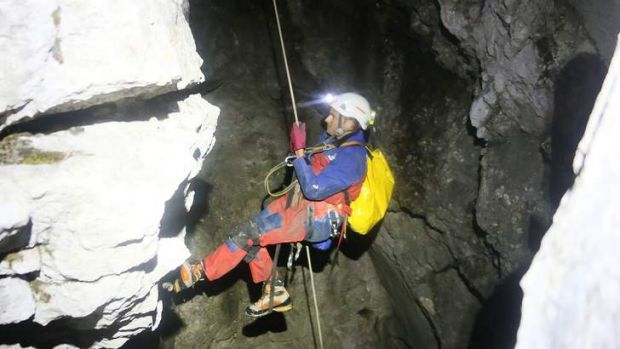 A rescuer abseils into the vast Riesending cave system.