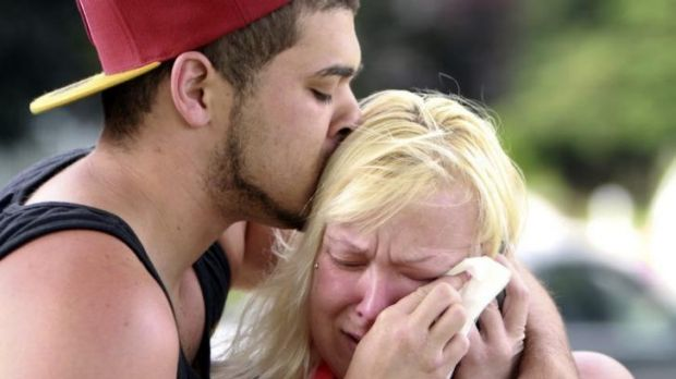 Two people comfort each other as they await word about the safety of students after a shooting at Reynolds High School.