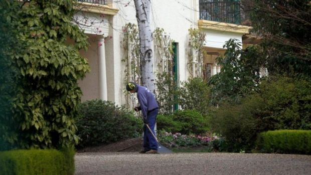 A gardener rakes the gravel driveway as the gates to The Lodge.