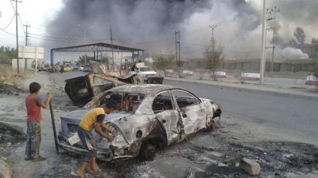 Children stand next to a burnt-out car during clashes between Iraqi forces and insurgents in the northern Iraqi city of ...