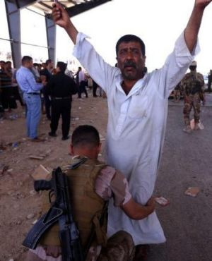 A security guard from Kurdish forces frisks a man fleeing the violence in Mosul.