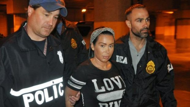 Samantha Barbash, centre, is escorted by police following her arrest in New York. Police allege Barbash is part of a ...