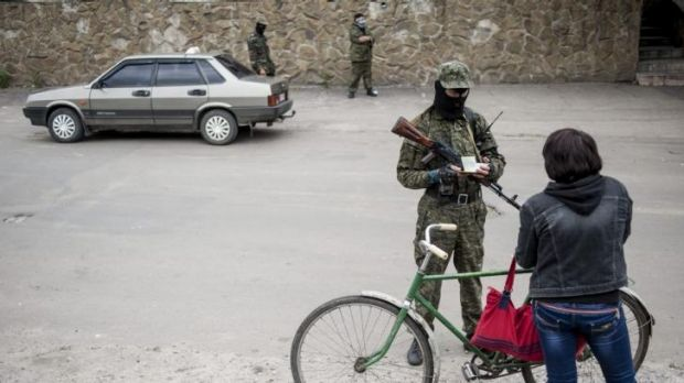 A pro-Russian fighter checks documents of a woman leaving the city at a checkpoint in Sloviansk.