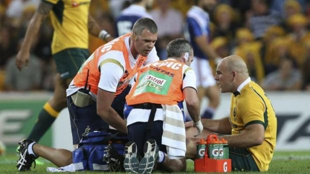 Emotional ride ahead: Stephen Moore receives treatment for his injury during the Test against France.