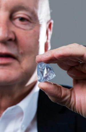 Petra chief executive Johan Dippenaar holding the 122.52 carat blue diamond.