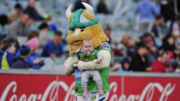Canberra Raiders mascot Victor the Viking holds Lily Arthur, 8 months, of Banks.