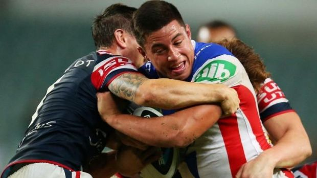 Newcastle's Joseph Tapine is well held by the Roosters' defence.