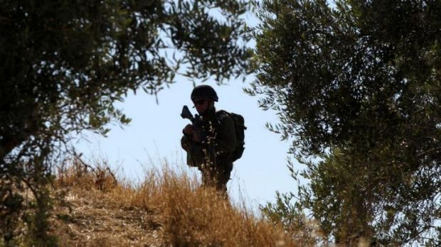 An Israeli soldier patrols an area at the entrance of the West Bank town of Hebron.