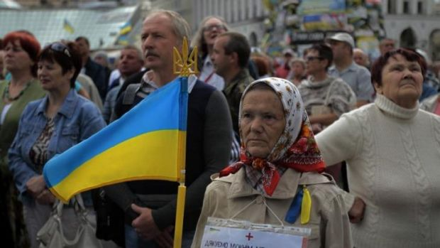 People gather during a rally in Independence Square in Kiev to mark Sunday's day of mourning after pro-Russia ...