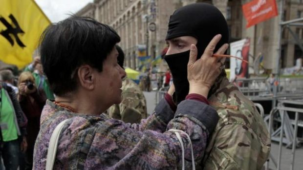 A woman speaks with a volunteer during a rally in Independence Square in Kiev on Sunday before the man set off for ...