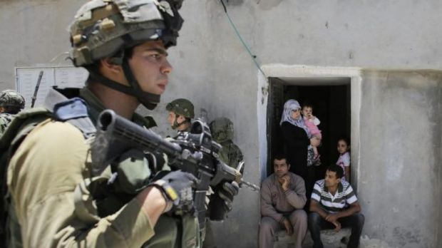 Palestinians sit outside their house as Israeli soldiers patrol near the West Bank City of Hebron.