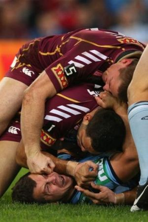 Brent Tate of the Maroons punches Greg Bird of the Blues during game three of the 2012 State of Origin series.