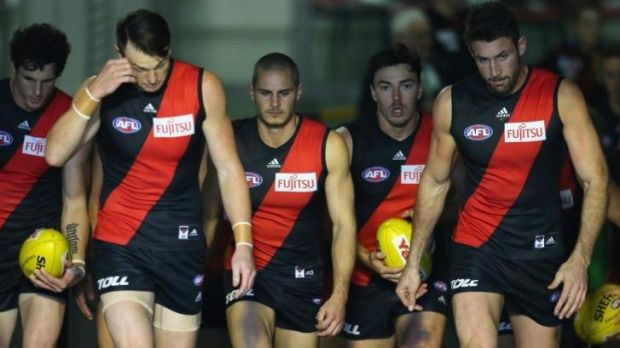 Distracted: Essendon players walk out for the game against Melbourne on Sunday.