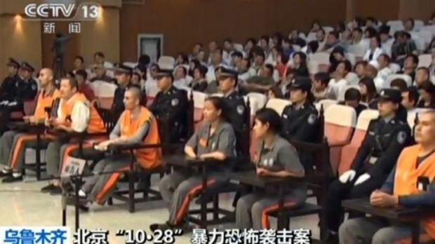 Six of the eight prisoners (seated - in orange and brown) in court in the Xinjiang capital Urumqi for the trial for ...