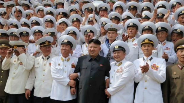Kim Jong-un, in black, posing with seamen during his inspection of the submarine.