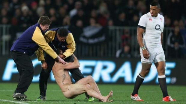 The streaker is manhandled during the All Black Test on Saturday night. The security guard on the right, Brad Hemopo, ...