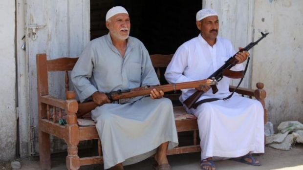 Iraqi men sit with their weapons in the Iraqi town of Jdaideh in  Diyala province on June 14 after they volunteered to ...