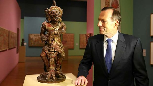 Soft diplomacy: Tony Abbott casts his eye over one of the treasures in Bali: Island of the Gods, after he opened the ...
