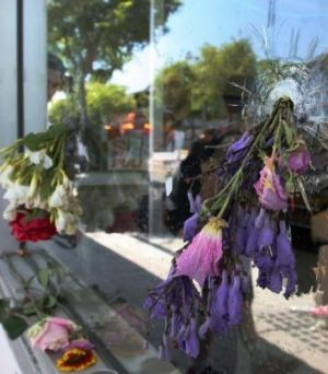 Flowers fill bullet holes in the shop front where Elliot Rodger fired shots.