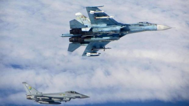 A Russian Sukhoi Su-27 fighter (top) is seen with a British Royal Air Force (RAF) Typhoon fighter as they fly in ...