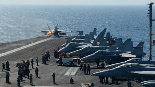 An image released by the US Navy shows an F-18 Hornet taking off from the flight deck of the USS George H.W. Bush in the ...
