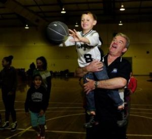 Bruce Minerds, who is trying to revive Canberra's Shadows indigenous basketball club, holds Isaiah Cornforth, 5, of Rivett.