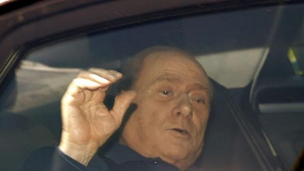 Silvio Berlusconi waves from his car as he leaves the Sacra Famiglia  community in Cesano Boscone, near Milan.