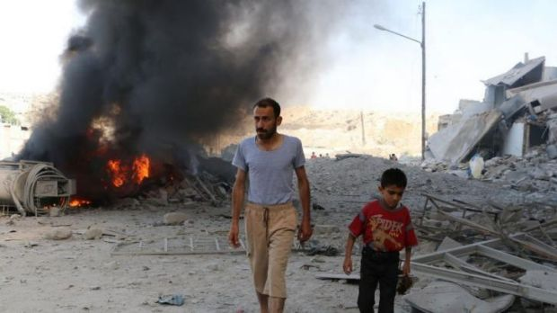 A man and a child walk past debris following a reported air strike by Syrian government forces.