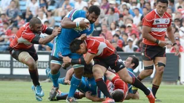 Italy's Manoa Vosawai is tackled by Japan's fullback Ayumu Goromaru and captain Michael Lieitch in Tokyo.