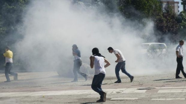 Ethnic Albanian protesters disperse as a tear gas canister thrown by Kosovo police lands during clashes in the ...
