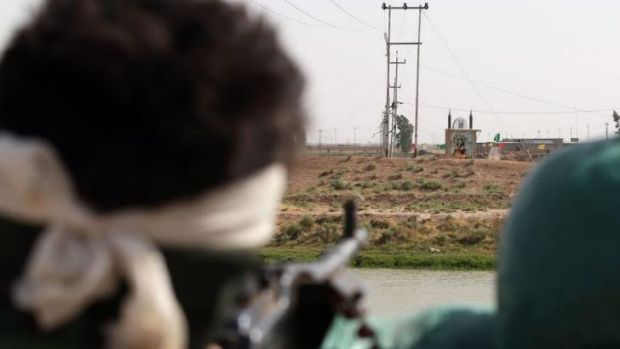 An Iraqi Turkmen fighter looks at an icon of the seventh century Imam Ali bin Abi Talib, 25 km south of Kirkuk. ISIL ...