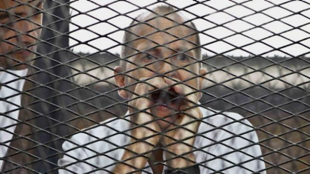 File photo: Australian correspondent of Al-Jazeera Peter Greste appears in a defendant's cage during his trial on terror ...