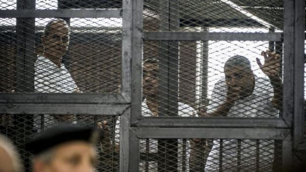 Peter Greste (left) and his colleagues Mohamed Fadel Fahmy and Baher Mohamed listen to the verdict from inside the ...