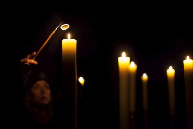 The candles are lit for In Praise of Darkness.