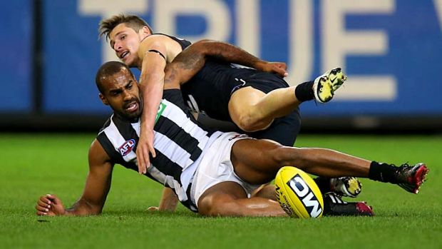 Collingwood's Heritier Lumumba under pressure from Andrejs Everitt.