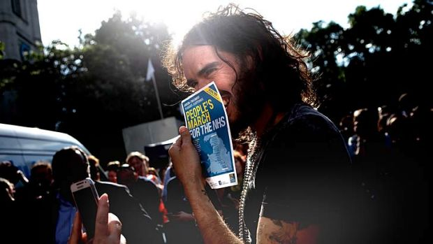 Comedian Russell Brand holds a flyer for a pro-NHS demonstration as he speaks to a members of a crowd that gathered in ...