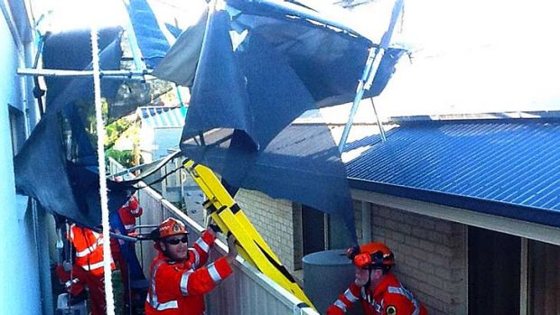 SES volunteers retrieve a trampoline from the roof of a house.